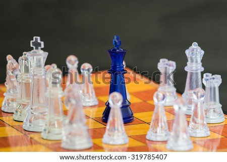 A blue king on the chess board surrounded by a number of transparent glass chess pieces. - Business competition concept. - stock photo