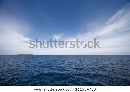 A blue ocean meeting a blue sky along a horizon. - stock photo