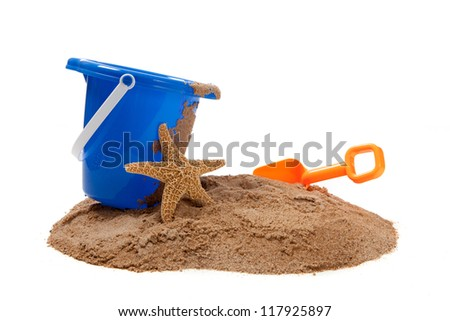 A blue pail and orange shovel with a starfish on a beach on a white background with copy space - stock photo