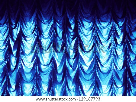 a blue shining curtain on the wall - stock photo