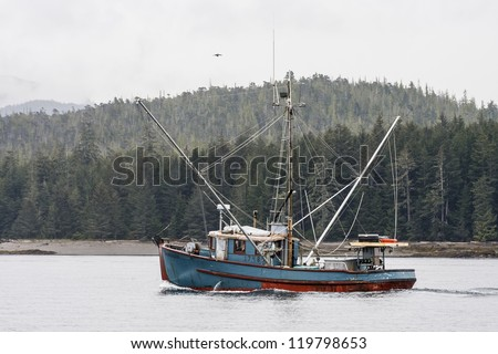 A blue shrimp boat trolling the grey waters of Alaska - stock photo