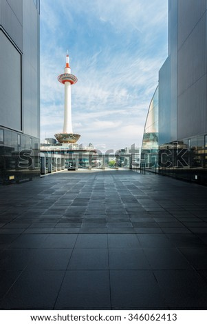 A blue sky with wispy clouds behind Kyoto Tower at daytime framed by modern lines and walls of a neighboring building balcony - stock photo