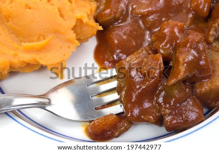 A blue striped plate with braised beef in a sauce and sweet potatoes with fork. - stock photo