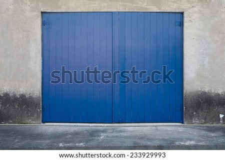 A Blue Wooden Door on Concrete Wall on A Concrete Platform. The Wall and Floor is Aged and Weathered. - stock photo