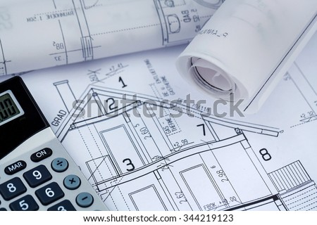 a blueprint of an architect with a calculator. symbolic photo for financing and planning of a new house. - stock photo
