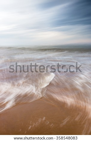 A blurred motion seascape featuring ocean waves and a dramatic overcast sky. - stock photo