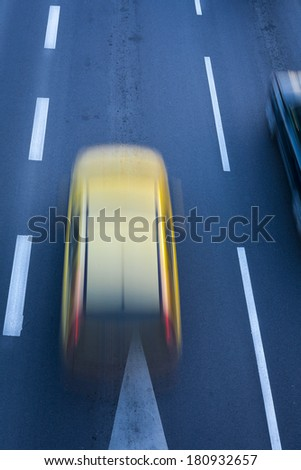 A blurred yellow car, speeding on the city road, white road lines. - stock photo