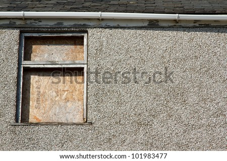 A boarded up window frame in bad repair with missing glass poor guttering a pebble dash wall and slate roof. - stock photo