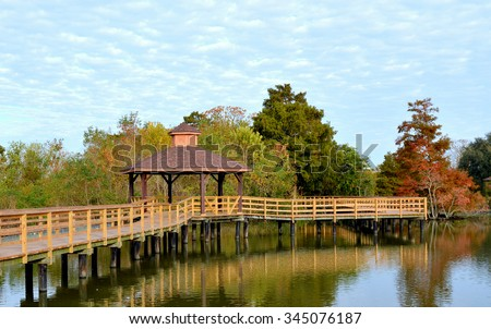 A boardwalk with a gazebo over a southern swamp in Lafreniere Park in Metairie, Louisiana. - stock photo