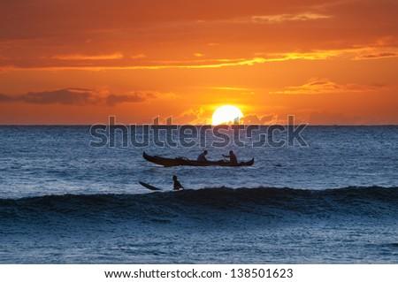 A boat and surfer at sunset, Maui, Hawaii, USA - stock photo