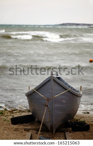 A boat at the seashore on a cloudy day - stock photo