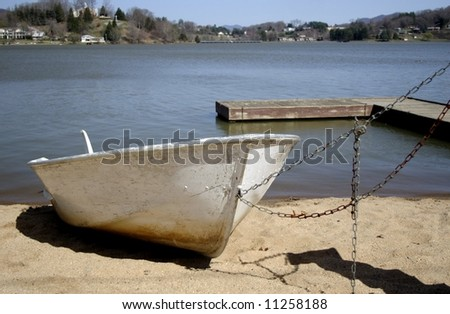 A boat beached on a lake shore for the winter - stock photo