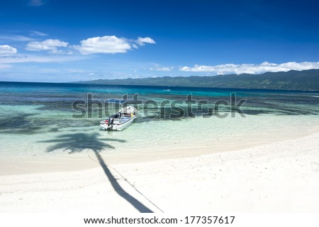A boat floats along the shore of a beautiful tropical beach with clear that shows a coral reef and highlights a deep blue vibrant sky.  - stock photo