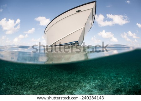 A boat floats in shallow water in the Caribbean Sea. This tropical region is a popular vacation destination for kayakers, divers, snorkelers, and recreational fishermen. - stock photo