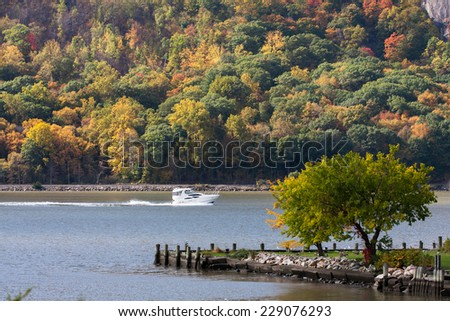 A boat going north on the Hudson River in Cold Spring, NY. - stock photo