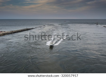 A boat headed through the Indian River inlet in Delaware at sunset. - stock photo
