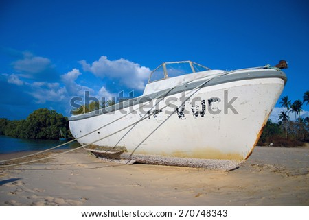 A boat lies on the sand on a beach. - stock photo