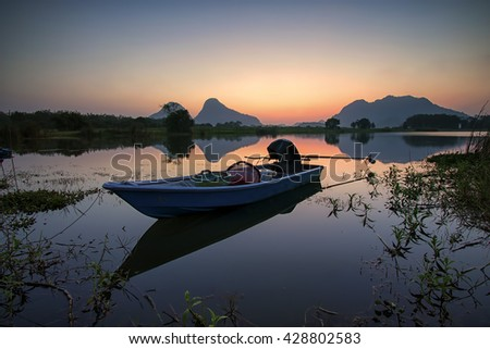 A boat parked at a lakeside during sunrise with hills in background - stock photo