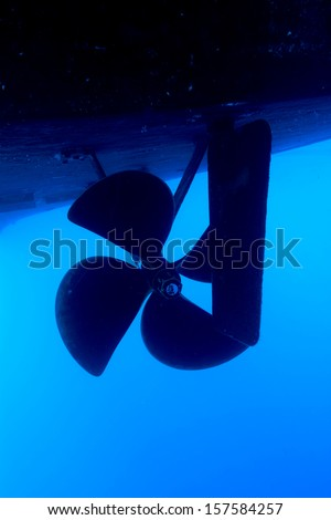 A boat propeller and rudder on a large vessel in blue water. - stock photo