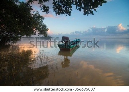a boat reflection during sunrise with burning sunrise on the sky - stock photo