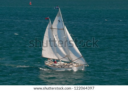 A boat with solitary captain sailing in the blue sea - stock photo