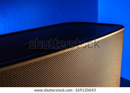 A bookshelf speaker is lit with golden light with a blue background light.  Differential focus on the centre of the lit part of the grill. - stock photo
