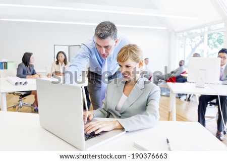 A Boss Guiding his Employee with her Job - stock photo