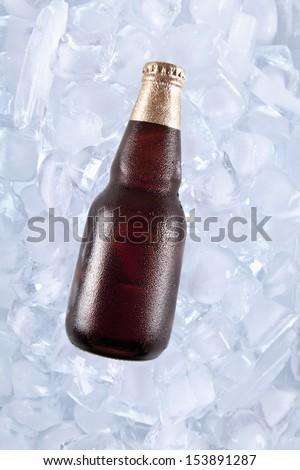 A bottle of dark beer on ice. - stock photo