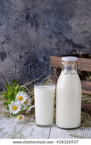 a bottle of milk and a glass of milk in a rustic table - stock photo