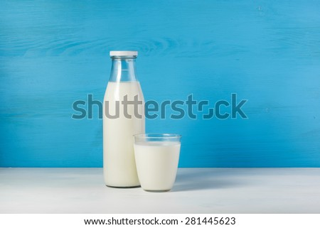 A bottle of rustic milk and glass of milk on a white table on a blue background, tasty, nutritious and healthy dairy products - stock photo