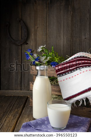 A bottle of rustic milk and glass of milk on a wooden table - stock photo