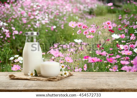 A bottle of rustic milk and glass of milk on a wooden table on flower garden background, tasty, nutritious and healthy 