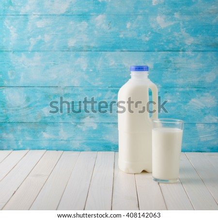 A bottle of rustic milk and glass on a wooden table with copy space - stock photo