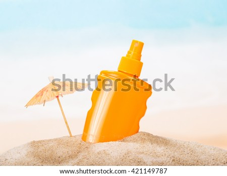 A bottle of sunscreen in the sand against the sea. - stock photo