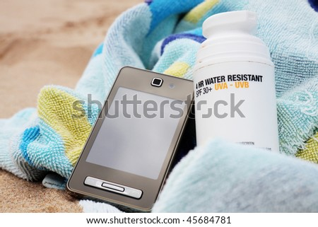 A bottle of sunscreen on a beach towel with mobile phone. Sandy background. - stock photo