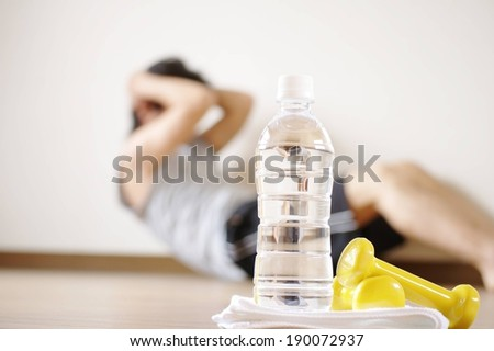 A bottle of water sitting beside two yellow weights with person working out in the background. - stock photo