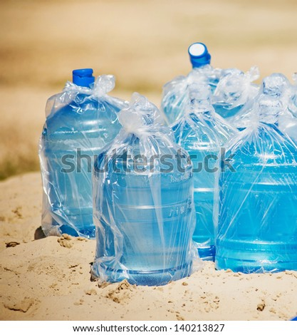 A bottle of water standing in sand at the beach - stock photo