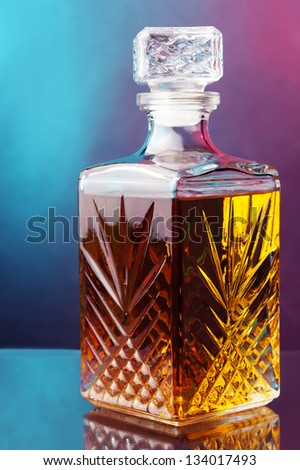 a bottle of whiskey against two color background - stock photo