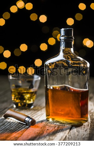 a bottle of whiskey and a vintage knife - stock photo