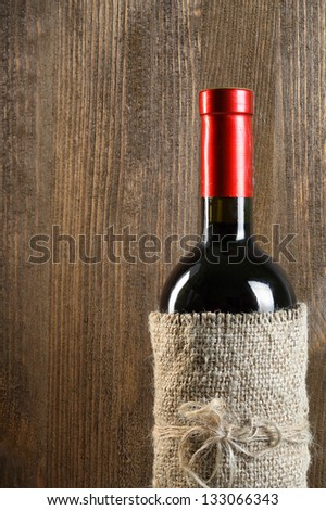 A bottle of wine on the wooden background - stock photo