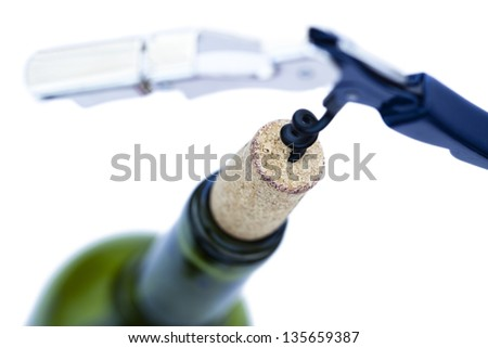 A bottled opener in the middle of extraction of the cork from its bottle. Seen from a high angle with a very shallow depth of field Isolated on white background. - stock photo