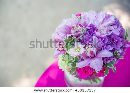 A bouquet made of violet flowers stands on the pink tablecloth - stock photo
