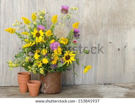 A bouquet of colorful prairie wildflowers in a metal container against an aged wooden background - stock photo