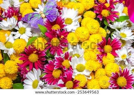 a bouquet of yellow roses and white flowers and purple butterfly - stock photo