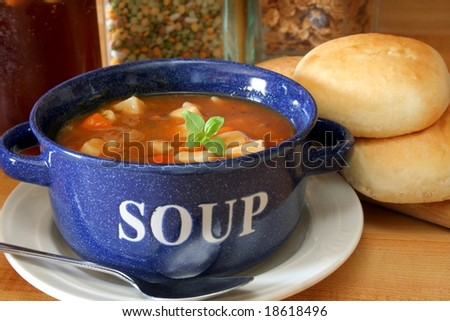 A bowl full of vegetable beef soup and fresh yeast rolls. - stock photo