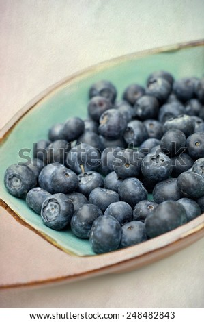 A bowl of blueberries, vertical close, blended with a textured background for painterly feel - stock photo