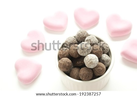 A bowl of candies, surrounded by pink heart shaped candies. - stock photo