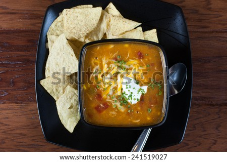 A bowl of chicken enchilada soup with white corn tortillas on the side. - stock photo