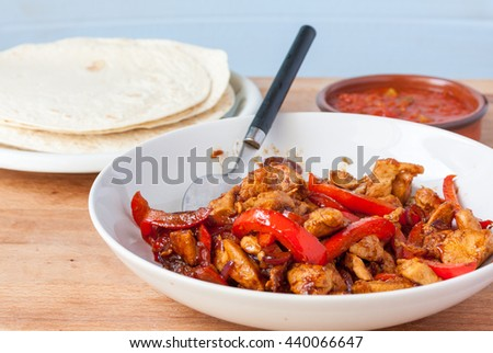 A bowl of chicken fajita mix with flour tortillas and salsa in the background - stock photo