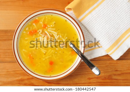 A bowl of chicken noodle soup on a rustic wooden table - stock photo